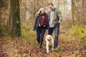 Paar geht mit Hund im Herbstwald spazieren.