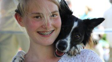 Mädchen und Hund schauen in die Kamera