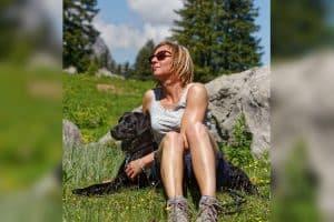 Frau entspannt mit Labrador in Natur
