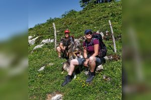 Zwei Wanderinnen und ihre Hunde machen eine Pause am Wegrand