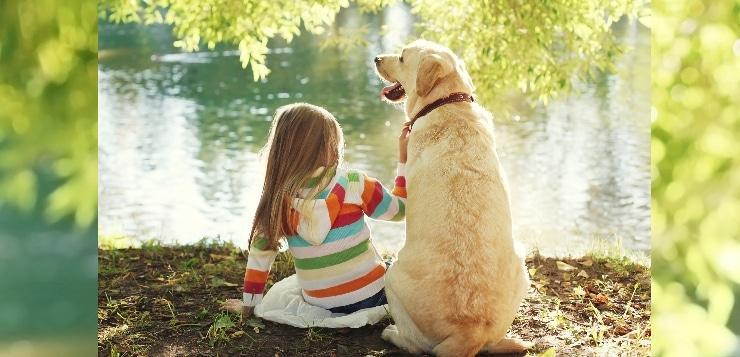 Kind und Hund sitzen nebeneinander an einem see