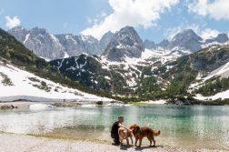 Frau mit Hunden an Gebirgssee