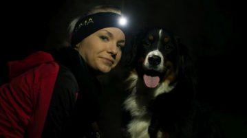 Frau und Hund schauen in Kamera. Die Frau trägt ein Stirnband mit LED-Lampe