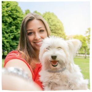 Junge Frau mit weißem kleinen Hund im Freien