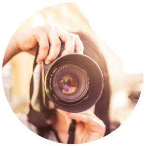 Frau hält Fotokamera vor dem Gesicht