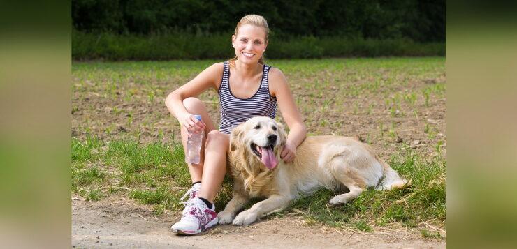 Frau hält eine Wasserflasche in der Hand und sitzt mit ihrem Golden Retriever am Wegrand, um eine Pause vom Training zu machen