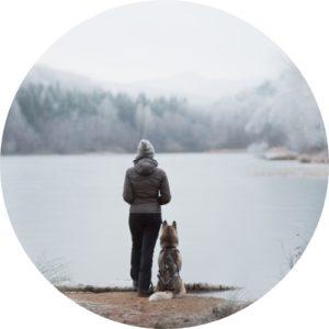 Frau und Husky stehen an zugefrorenem See