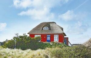 Rotes Ferienhaus mit blauer Tür und Reetdach