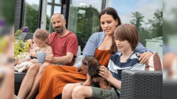 Eine Familie mit 2 Kindern und einem Dackel sitzen auf einem Outdoor-Sofa